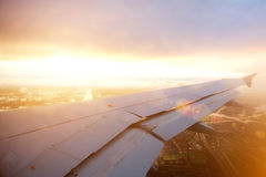 Airplane wing descending through the clouds at sunset Stock Image