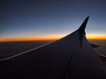 Airplane wing at dusk, colorful skyline Royalty Free Stock Images