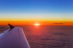 Airplane wing in flight above the clouds at the sunset background Stock Photos