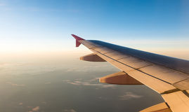 Airplane Wing in Flight from window with sunset sky Stock Images