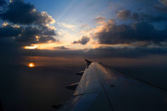 Airplane Wing in Flight from window, sunset sky Royalty Free Stock Photos