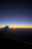Airplane Wing in Flight from window, sunset sky Royalty Free Stock Photography