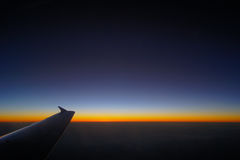 Airplane Wing in Flight from window, sunset sky Royalty Free Stock Photo