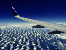 Airplane wing flying above clouds Royalty Free Stock Photography