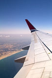 Airplane wing flying above the seashore. Royalty Free Stock Photography