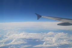 Airplane wing flying in a blue sky Stock Photo