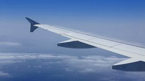 Airplane wing flying over clouds in blue sky stock video footage