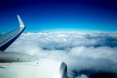 Airplane wing flying over fluffy clouds in blue sky Royalty Free Stock Photos