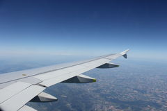Airplane wing flying over land Stock Image