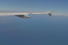 Airplane wing in front on blue sky. Royalty Free Stock Photography