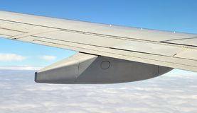 Airplane wing with fuel tanks over the clouds Stock Photos
