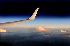 Airplane wing high up at dusk. Stock Photos