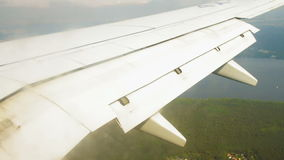 Airplane wing during landing with flaps down on the sky over land.  stock footage
