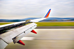 Airplane Wing in Motion. Airplane wing open upon landing on runway in motion stock photography