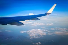 Airplane wing out of window. Sky and cloud as seen through window of an aircraft Royalty Free Stock Photo