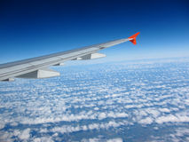 Airplane wing over clouds Royalty Free Stock Images