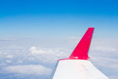 Airplane wing over the clouds Stock Photos