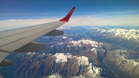 Airplane wing over snow capped peaks