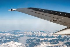 Airplane wing over snowy mountains stock image