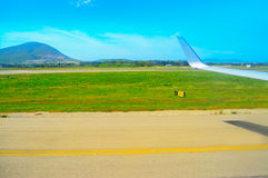 Airplane wing over a taxiway Royalty Free Stock Photo
