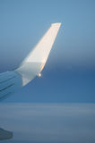 Airplane wing with sky. The white tip of a airplane wing in soft sunset light against a beautiful blue gradient sky. Portrait orientation, with copy space stock photos