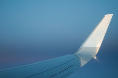 Airplane wing with sky. The white tip of a airplane wing against a beautiful blue gradient sky. With copy space Stock Photography