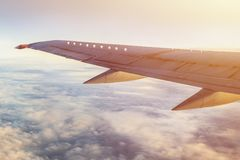 Airplane wing in sky with clouds and sun shine. Traveling by airlines promotion background Royalty Free Stock Images