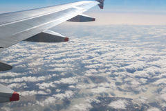 Airplane Wing on The Sky. Wing of an airplane flying above the cloud stock photo
