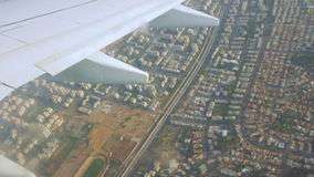 Airplane wing on the sky and over land with building of Tel Aviv. City and the Mediterranean sea stock video footage