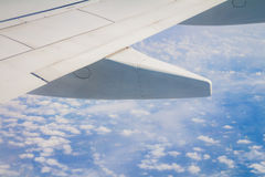 Airplane wing on the sky and over sea with clouds Royalty Free Stock Image