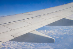 Airplane wing on the sky and over sea with clouds Stock Image