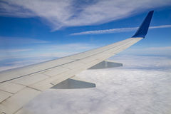 Airplane wing on the sky and over sea with clouds Stock Images