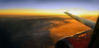 Wing of an airplane flying at sunset. Wing of an airplane jet flying above the clouds at sunset Royalty Free Stock Image