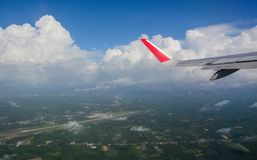 Wing of civil aircraft. Airplane wing view. An aircraft flying over green fields Stock Photography