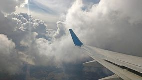 Airplane wing view out of the window on the cloudy sky background. Holiday vacation background. Wing of airplane flying above. The clouds in the blue sky stock photo