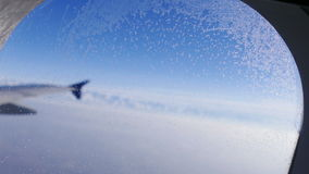 Airplane Wing Window Hoarfrost Blue Sky 4k. Travel concept: hoarfrost on the aircraft window on the background of the plane wing and blue sky stock video footage