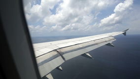 Airplane wing through window over Indian Ocean stock video footage