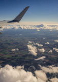 Airplane Winglet above clouds. High up view on clouds, land, and wing tip from airplane porthole Royalty Free Stock Photo