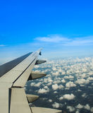 Airplane wings in the blue clouds Stock Photo