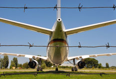 Airplane and wire. Airplane behind three lines of barbwire Stock Image