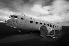 Airplane wreck on a black beach in south of Iceland. Black and white horizontal side view of a plane wreck on black sands and background of blue sky in south of Stock Images