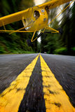 Airplane. Yellow airplane landing on a road in the forest Stock Photo
