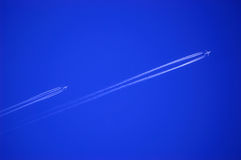 Airplanes. Two jet airplanes at high altitude with vapor trail behind in the deep blue sky Royalty Free Stock Image
