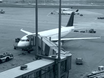 Airplanes at airport. Airplanes at an airport and a jetway stock image