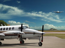 Airplanes on airport. The private luxury airplane is parked on airport and other is landing on. The airport field, runway, tropical sea and cloudscape as the stock photos