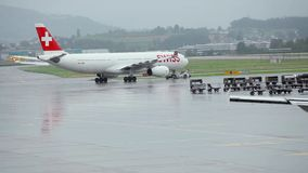 Airplanes at the airport. Two aircraft - one parked at the airport, and another - a plane taking off. At the tail of the aircraft flag of Switzerland. Passenger stock video footage