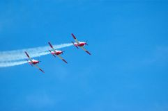 Airplanes at airshow. Three airplanes in red and white flying in the air performing at an airshow Royalty Free Stock Photography