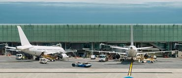Airplanes on busy airport. Panorama. Airplanes are parked in airport. Cargo loading and tecnical service is in progress. Panorama. The sky area, surface of the royalty free stock images