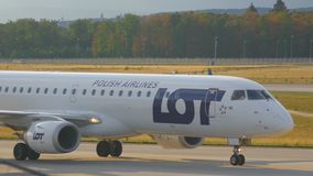 Airplanes in Frankfurt Airport. FRANKFURT AM MAIN, GERMANY - SEPTEMBER 5, 2015: Lufthansa Airbus 320 D-AIZO braking after landing at 25R and LOT Embraer 195 SP stock video footage