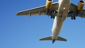 Airplanes landing and takes off at airport. View on medium sized white airplane with two yellow tourbines passing over head, isolating at clean blue sky stock footage